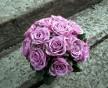 Kulatá svatební kytice z fialových růží doplněných skleněnými korálky