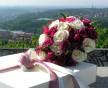 Kulatá svatební kytice v netradiční kombinaci světlých a tmavých růží