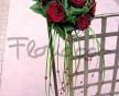 Svatební kytice z rudých sametových růží s převisem trávy a navlečených rudých korálků
